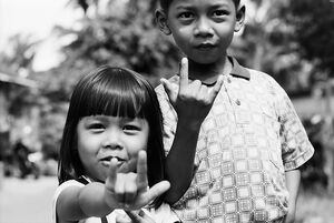 Siblings raising index finger and little finger