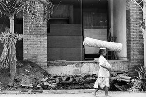 Woman walking putting large thing on head
