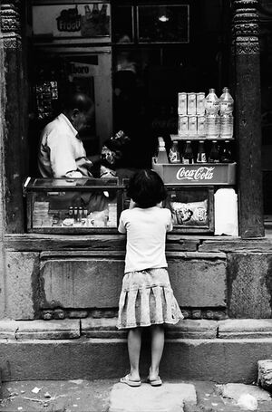Girl buying candies in small shop