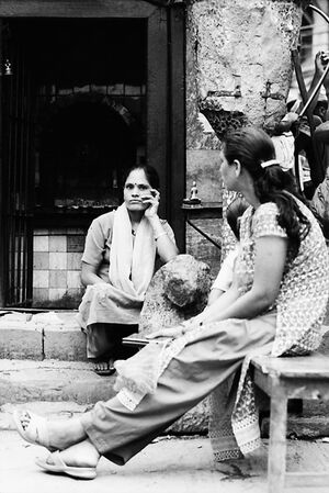 Women sitting in front of small Hindu shrine