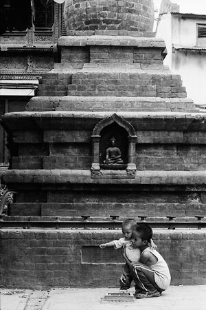 Boy looking after little brother in front of Buddha statue