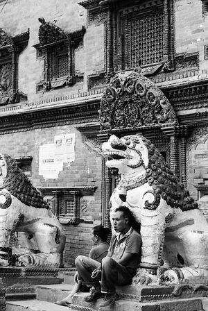 獅子像に寄りかかる男