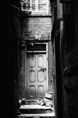 Wooden door in dim alleyway