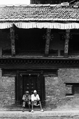 木製の扉の前に並んで腰を下ろした二人の男