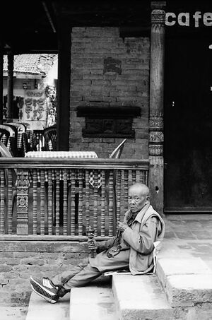 Old monk holding prayer wheel