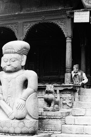Man sitting behind stone statue