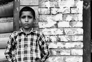 Boy standing against brick wall