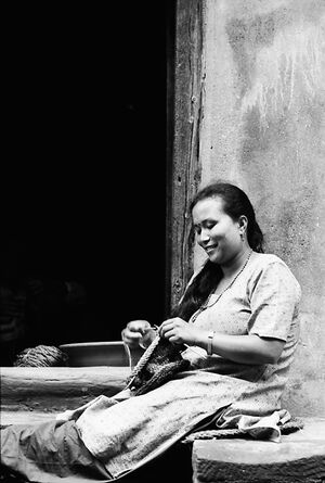 Woman sitting knitting in front of door