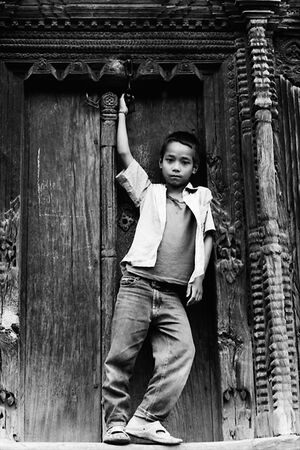 Boy striking pose in front of wooden door