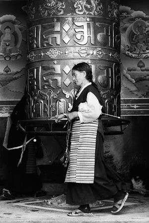 Older woman turing around big prayer wheel