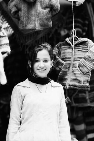 Young woman standing in front of sweaters
