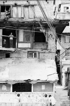 2階の窓辺に立つ女の子