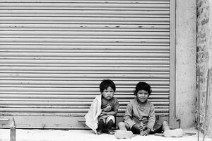 Kids sitting in front of shutter