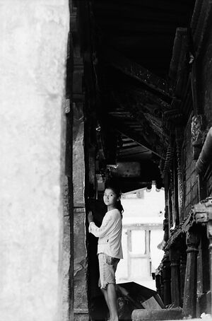 Girl looking back in corridor of temple