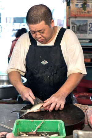Fishmonger cutting fish