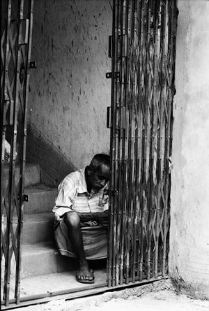 Man sitting behind shutter