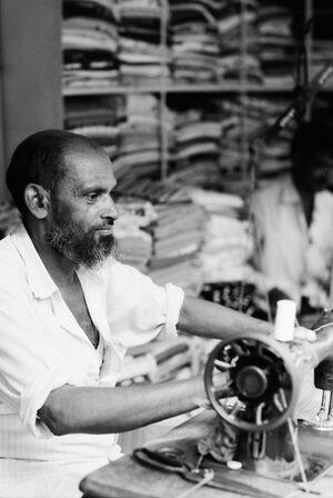 Man operating sewing machine