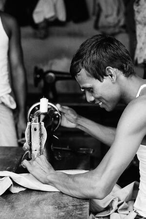 Man manipulating sewing machine