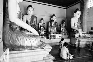 Women surrounded by Buddha statues