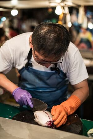 魚を捌く魚屋の男