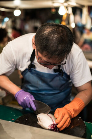 Fishmonger cutting a fish