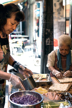 Women making rolled sushi