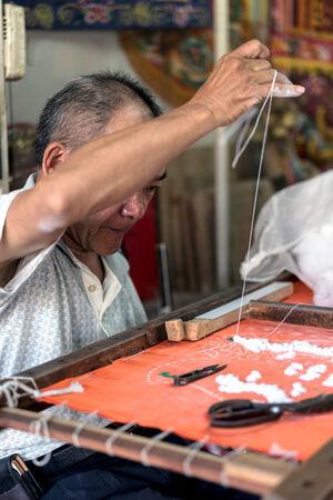 man stitching banner