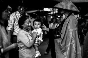 Monk stroking baby's head
