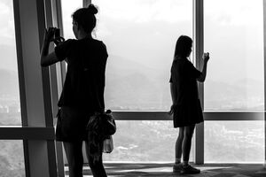 Two silhouetted women taking photos