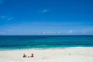 Two women on white sand beach