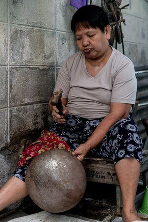 バーン・バートで托鉢用の鉢を叩く女