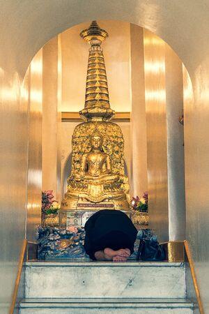 Woman bowing down on knees in Wat Saket