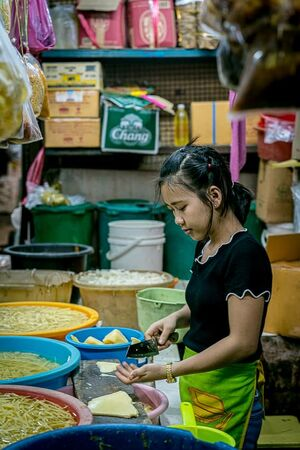 Young woman cutting vegetables in Khlong Toei Market