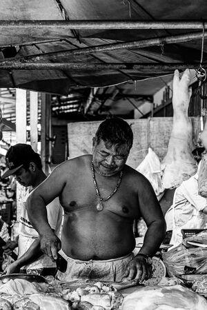 豚肉を捌く男