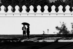 Silhouettes standing under same umbrella