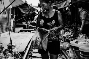 Woman walking on railroad track in Maeklong Railway Market