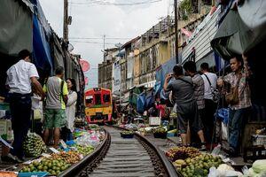 Train running in Mae Klong Railway Market