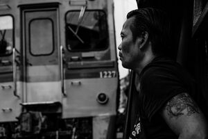 Train and man in Mae Klong market