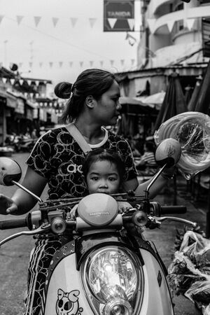 Little girl riding motorbike with mother