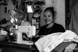 Woman working with power-operated sewing machine