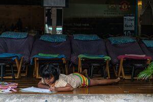 寝そべりながら勉強する女の子