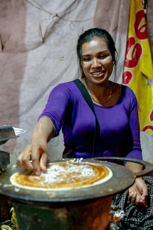 Woman cooking Dosa by the roadside