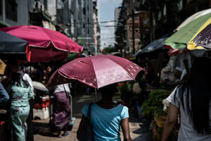 Woman walking street market with umbrella