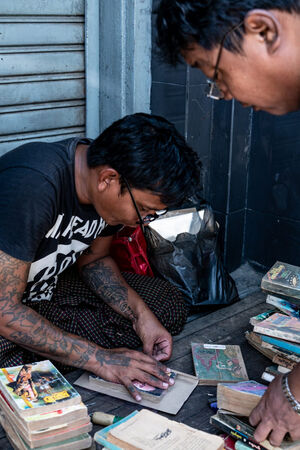 Man repairing an used book by the wayside