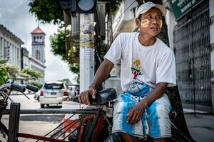 Pedicab driver waiting for customers in a street corner