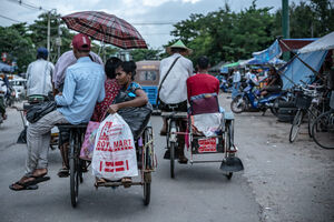 Pedicabs running street with passengers