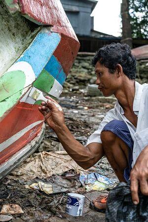 漁船を塗り直していた男