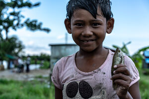 Girl holding small fish in her hand
