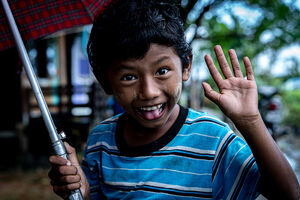 Boy smiling while holding umbrella