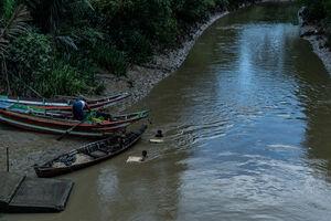 木造ボートと川を泳ぐ男の子